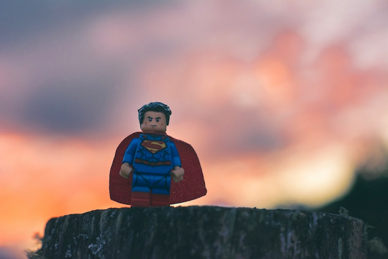 A Lego Superman proudly standing on a rock