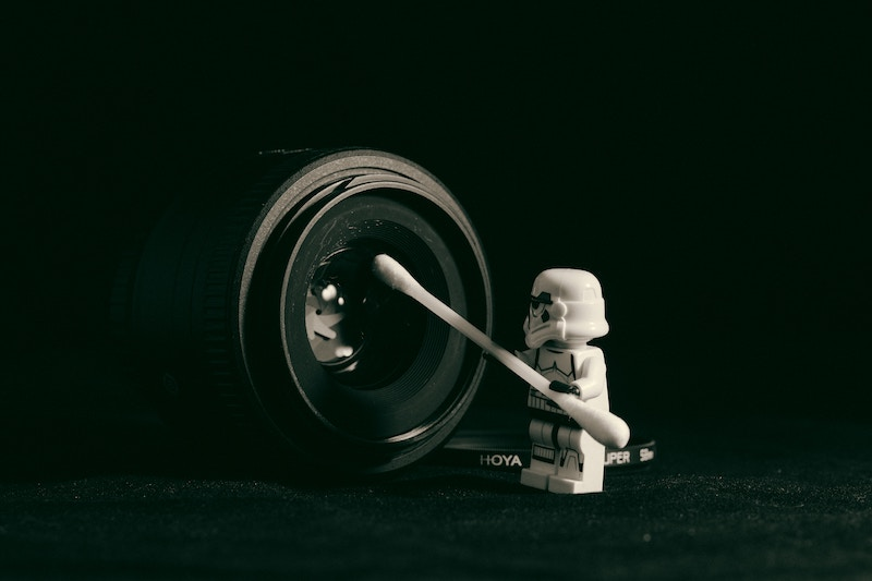 A Lego trooper cleaning the lens of a DSLR camera