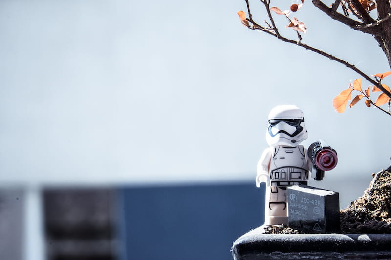 Lego trooper standing under a tree with a weapon